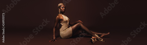 Fototapeta  seductive african american woman with short hair posing in glamorous dress on br