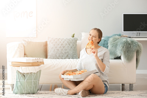 Beautiful woman eating tasty pizza at home