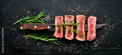 Fotografia  Juicy Steak on the knife. Top view. Free space for your text.