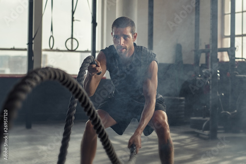 Poster Echelle de hauteur Young man exercising using battle rope
