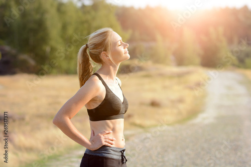 Foto  Sporty woman enjoys the sun after running and workout on a sunny summer day