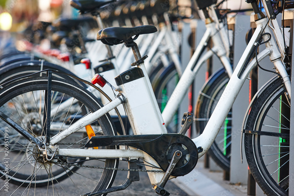 Fototapety, obrazy: Charging urban electric battery bikes in the city. Eco transport