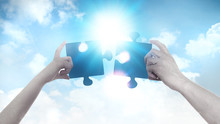 Two Hands Holding A Puzzle Pieces Agains Of Blue Sky Background And Sun. Business, Support, Finding The Right Decision Concept.