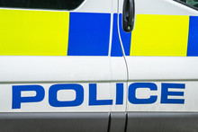 Fragment Of A White Police Car With A Word POLICE Spelled Out In Blue In England , Close Up