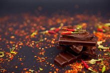 Black Chocolate With Peppers On The Black Background.
