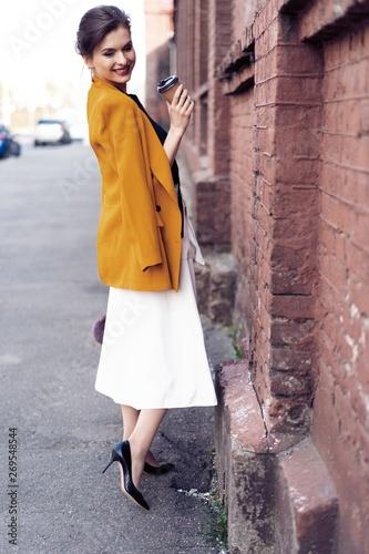 Spoed Foto op Canvas Gypsy Portrait fashion woman walking on street . She wears yellow jacket, smiling to side.