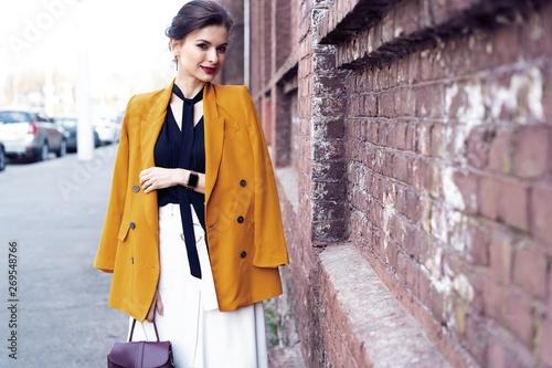 plakat Portrait fashion woman walking on street . She wears yellow jacket, smiling to side.