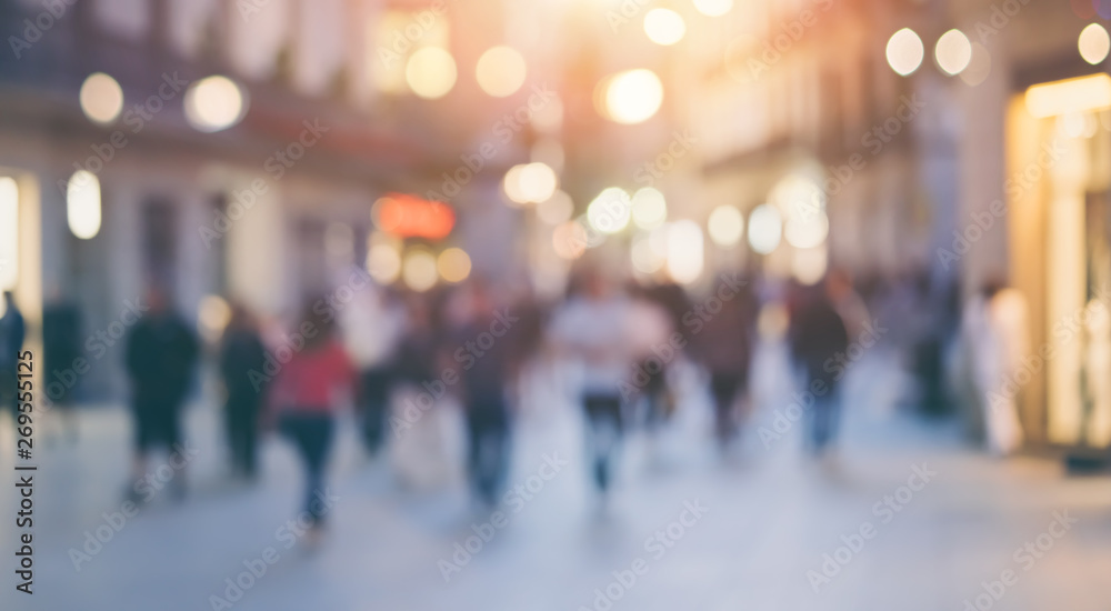 Fototapety, obrazy: Group of unrecognizable anonymous people in bokeh walking on a street in the evening. Defocused image