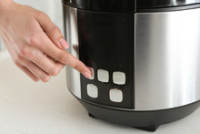 Woman Switching On Modern Multi Cooker On Table, Closeup