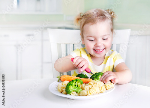 Obraz Child girl sitting at table with a plate of food,kid eating vegetables. - fototapety do salonu