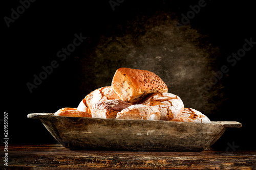 Fresh tasty bread on wooden plate and free space for your decoration.