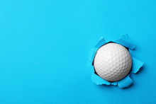 New Golf Ball Stuck In Color Paper. Space For Text