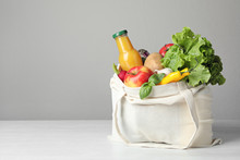 Cloth Bag With Vegetables And Bottle Of Juice On Table Against Grey Background. Space For Text