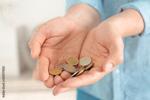 Fotografie, Obraz  Man holding coins in hands indoors, closeup