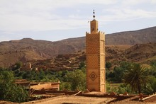 View On Old Berber Arabian Village With Clay Brick Houses In Valley With Greenery And Minaret