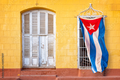 Canvastavla  Cuban flag hanging at the window of a colorful house in a street of Trinidad, Cu