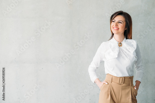 Obraz Smiling business lady hands in pockets. Beautiful successful female looking into distance. Prosperity contentment delight. - fototapety do salonu