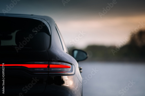 Fototapeta Modern suv car rear taillamp at evening near lake