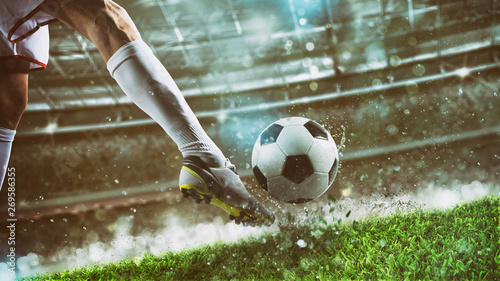 Fotografia Football scene at night match with player ready to shoot the ball