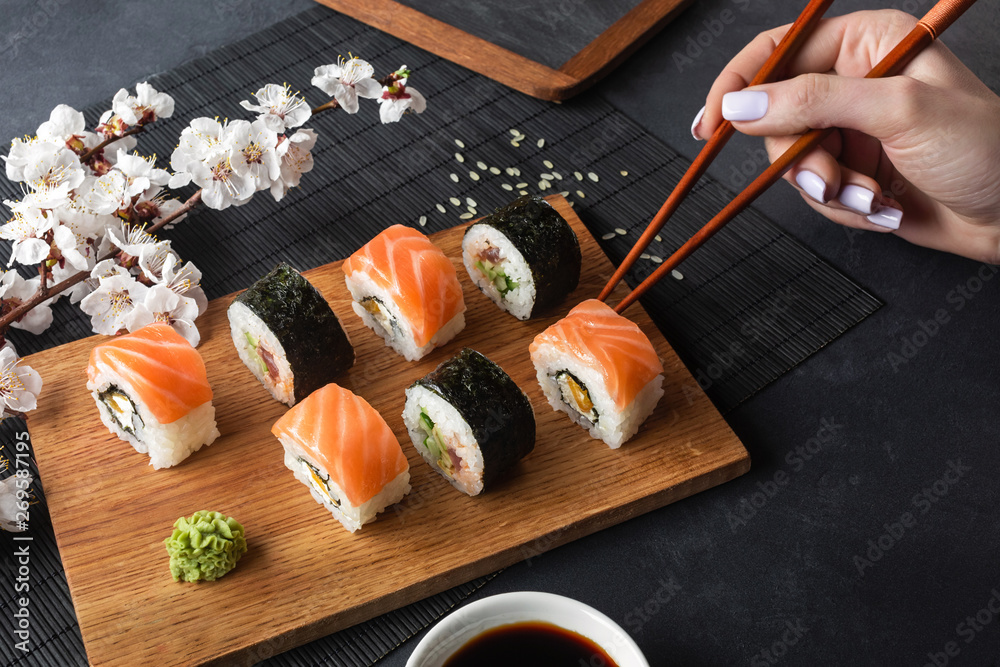 Fototapety, obrazy: Set of sushi and maki rolls, hand with chopsticks and branch of white flowers on stone table