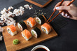 Set of sushi and maki rolls, hand with chopsticks and branch of white flowers on stone table