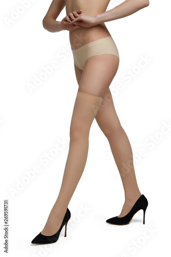 Cropped half-turn view of lady's legs, wearing skin colored nylon stockings and black pumps with high heels Canvas Print