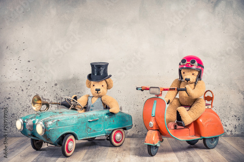 Teddy Bear in antique cylinder hat driving rusty retro toy pedal car from circa 60s and Teddy Bear in red helmet with goggles sitting on old orange children's scooter. Vintage style filtered photo