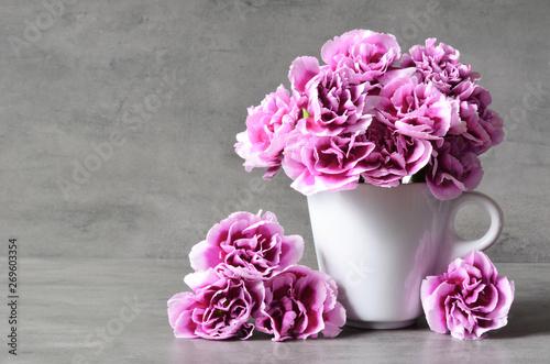 Obraz Różowe goździki kwitnące w filiżance na szarym tle - fototapety do salonu