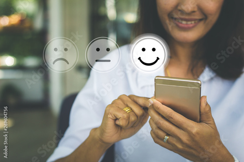 Photographie Businesswoman pressing face emoticon on virtual touch screen at smartphone