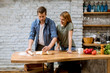 canvas print picture - Young couple caking pizza in kitchen together