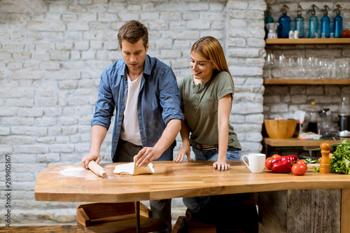 Photo  Young couple caking pizza in kitchen together