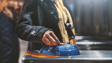 Close-up View Of A Hand Of A Female Tourist Putting A Ticket Onto A Blue Magnet Electronic Area Of A Chromed Turnstile In The Subway Or A Railway Station Depot, Selective Focus, Shallow Depth Of Field