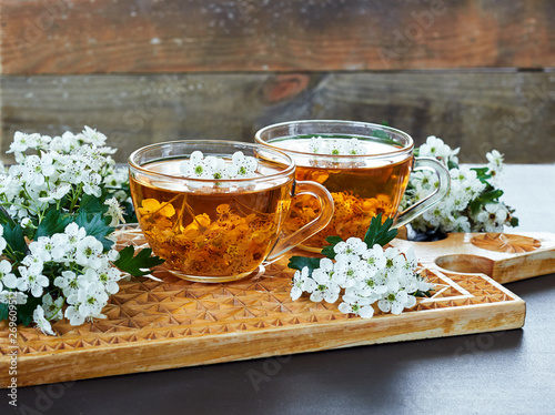Photo Pair of herbal healing flower tea from hawthorn bloom with blossom of  a tree ne