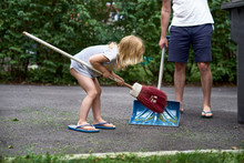 Little Girl Helps Her Parents Collect Grass In The Yard. Seasonal Gardening. Cleaning The Yard