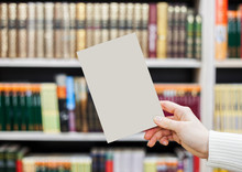 Collection Of Various White Paper On White Background. A Book Under The Library.