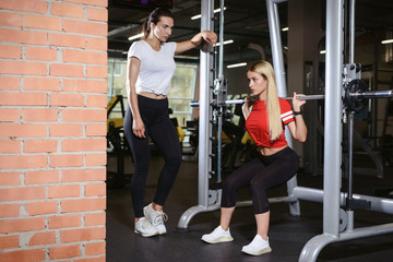 Beautiful fitness young girl doing squats with the barbell in smith machine at the gym. Personal trainer cheering her and making assistance. Perfect fitness female figure