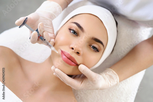Lips injection. Syringe with filler for lips contouring or augmentation. Mode...