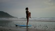 beautiful young fit surfer woman does yoga fitness on the beach at sunrise. Slow motion.