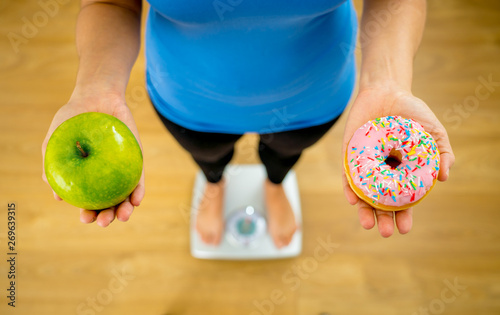 Fotografia, Obraz Woman on scale measuring weight holding apple and donuts choosing between health