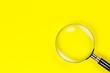 Leinwandbild Motiv magnifying glass on yellow