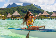 Outrigger Canoe - Woman Paddling In Traditional French Polynesian Outrigger Canoe For Recreation Sport Watersport Competition. Bora Bora With Mount Otemanu And Overwater Bungalow Resort Hotel.