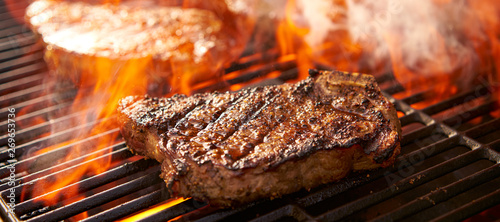 rib-eye steaks cooking on flaming grill panorama