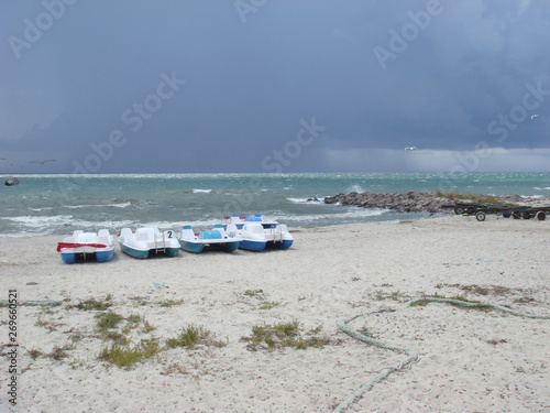 In de dag Inspirerende boodschap Cloudy sky over the sea. Storm clouds forming over clear sea. Catamarans on a sandy beach