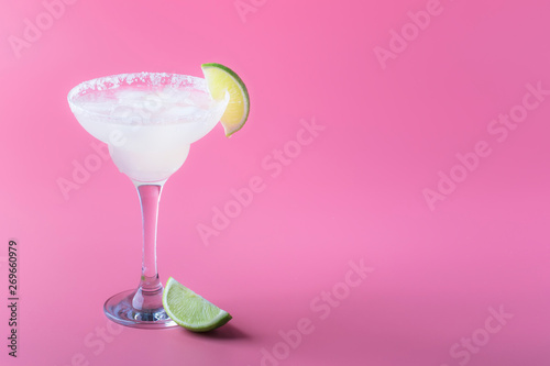 Classic margarita alcohol cocktail with tequila, liqueur, lime juice, sugar syrup, salt and ice, summer pink background, place for text