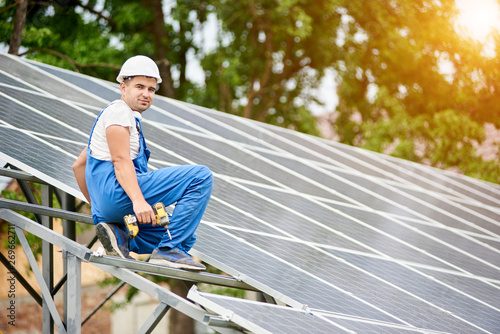Young smiling electrician worker sitting on almost finished stand-alone solar photo voltaic panel system on bright sunny green tree background. Alternative energy concept.