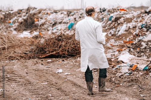 Valokuvatapetti Full length of Caucasian ecologist in white uniform estimating pollution on landfill