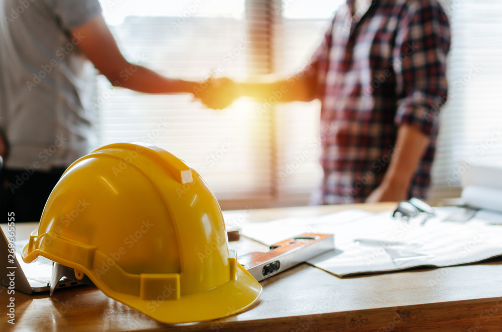 Fototapety, obrazy: yellow safety helmet on workplace desk with construction worker team hands shaking greeting start up plan new project contract in office center at construction site, partnership and contractor concept