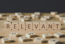 Selective Focus Of Relevant Inscription On Cubes Surrounded By Blocks With Letters On Wooden Surface Isolated On Black