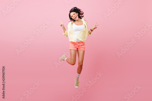 Blissful slim latin girl in casual bright attire enjoying leisure time in studio. Graceful asian woman in sunglasses funny jumping near pink wall. - 269667926