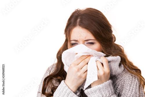 Obraz na plátně  Sick freezing woman sneezing in tissue